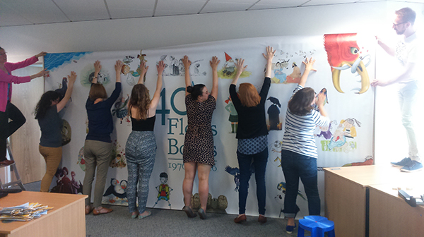 """It's all hands on deck as the team work hard to install the """"Great Wall of Floris Books""""!"""