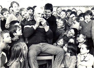 Photograph of Duncan Williamson playing music for children