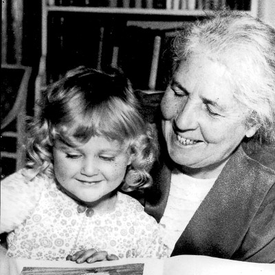 Photograph of Elsa Beskow, author of Swedish children's books, reading with a young child