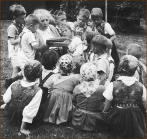 Photograph of Elsa Beskow, Swedish children's author and illustrator, reading to a large group of children